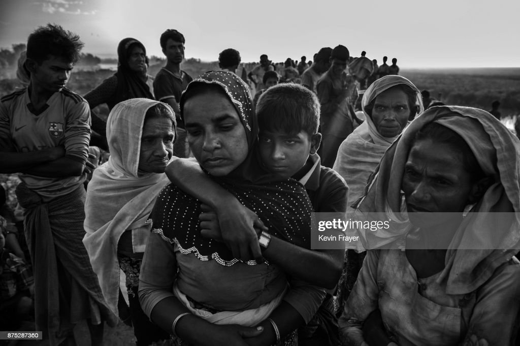 COX'S BAZAR, BANGLADESH - NOVEMBER 03: Rohingya Muslim refugee Hasna Begum is embraced by her son Mohammad Ayaz, 13 years, as they and others wait to proceed to camps after crossing the border from Myanmar into Bangladesh close to the Naf River on November 3, 2017 near Anjuman Para in Cox's Bazar, Bangladesh. More than 600,000 Rohingya refugees have flooded into Bangladesh to flee an offensive by Myanmar's military that the United Nations has called 'a textbook example of ethnic cleansing'. The refugee population continues to swell further, with thousands more Rohingya Muslims making the perilous journey on foot toward the border, or paying smugglers to take them across by water in wooden boats. Hundreds are known to have died trying to escape, and survivors arrive with horrifying accounts of villages burned, women raped, and scores killed in the 'clearance operations' by Myanmar's army and Buddhist mobs that were sparked by militant attacks on security posts in Rakhine state on August 25, 2017. What the Rohingya refugees flee to is a different kind of suffering in sprawling makeshift camps rife with fears of malnutrition, cholera, and other diseases. Aid organizations are struggling to keep pace with the scale of need and the staggering number of them - an estimated 60 percent - who are children arriving alone. Bangladesh, whose acceptance of the refugees has been praised by humanitarian officials for saving lives, has urged the creation of an internationally-recognized 'safe zone' where refugees can return, though Rohingya Muslims have long been persecuted in predominantly Buddhist Myanmar. World leaders are still debating how to confront the country and its de facto leader, Aung San Suu Kyi, a Nobel Peace Prize laureate who championed democracy, but now appears unable or unwilling to stop the army's brutal crackdown.