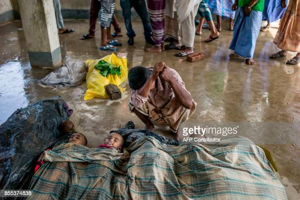 A Rohingya Muslim refugee mourns beside the bodies of his three children at a school near Inani beach in Cox's Bazar district on September 29 2017...