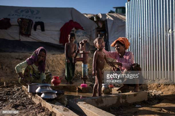 A Rohingya Muslim refugee washes a child at a water pump in the Kutupalong refugee camp in Cox's Bazar on December 4 2017 Rohingya are still fleeing...