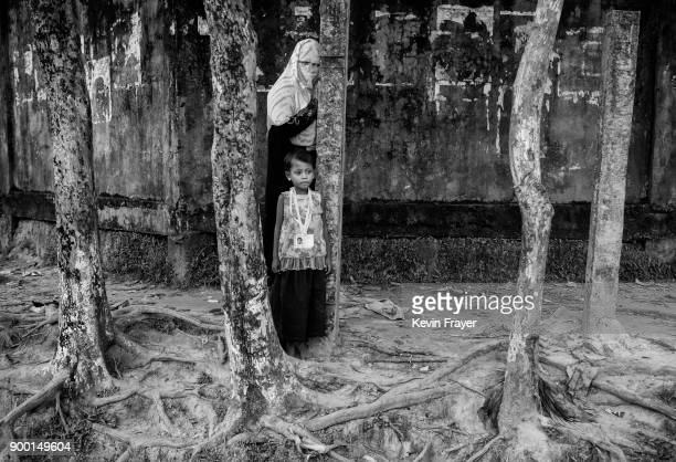 COX'S BAZAR BANGLADESH OCTOBER 25 A Rohingya Muslim refugee woman and child wait outside a registration centre on October 25 2017 near the Kutapalong...