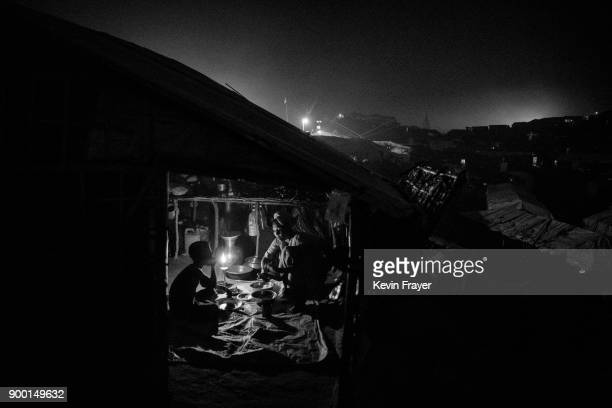 COX'S BAZAR BANGLADESH OCTOBER 25 A Rohingya Muslim refugee woman and her child eat dinner by candlelight in their makeshift shelter on October 25...