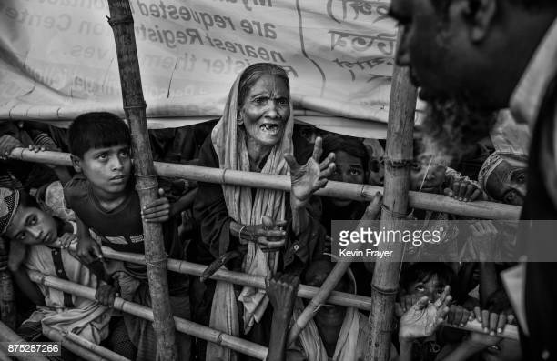 COX'S BAZAR BANGLADESH OCTOBER 24 A Rohingya Muslim refugee woman begs for food aid as she waits with others behind a barricade at a distribution...