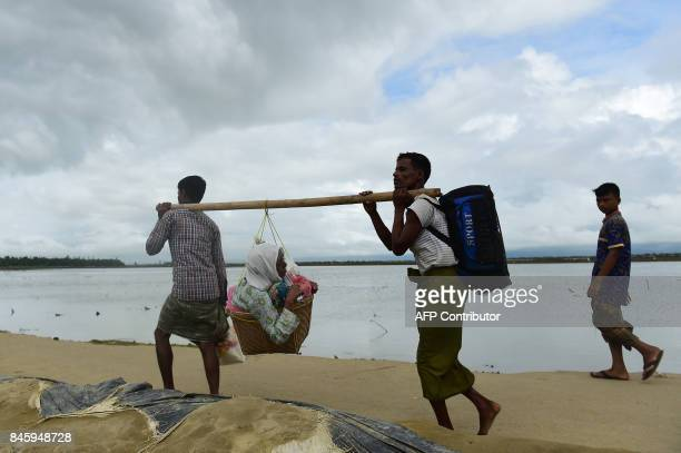 Rohingya Muslim refugees carry an elderly relative as they arrive from Myanmar after crossing the Naf river in the Bangladeshi town of Teknaf on...