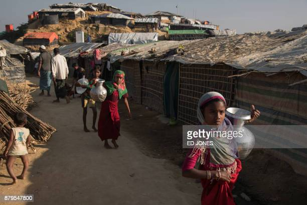 Rohingya Muslim refugees carry water through the Kutupalong refugee camp in Cox's Bazar on November 26 2017 Rohingya refugees who return to Myanmar...