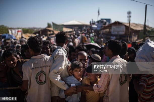 TOPSHOT Rohingya Muslim refugees children queue for aid suplies at the Kutupalong refugee camp in Cox's Bazar on December 4 2017 Rohingya are still...