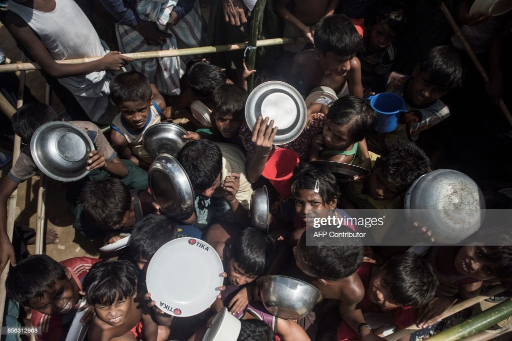 Rohingya Muslim refugees children rush to line up at a food distribution in Balukhali refugee camp near Gumdhum on September October 1, 2017. Bangladesh is to move to a camp at least 15,000 Rohingya refugees who have settled in a restive hill district near the border with Myanmar, a local official said Sunday. Most of the estimated half a million Rohingya who have arrived in southeastern Bangladesh over the last five weeks after fleeing violence in Myanmar are crammed into the camps that have sprung up on government land. /