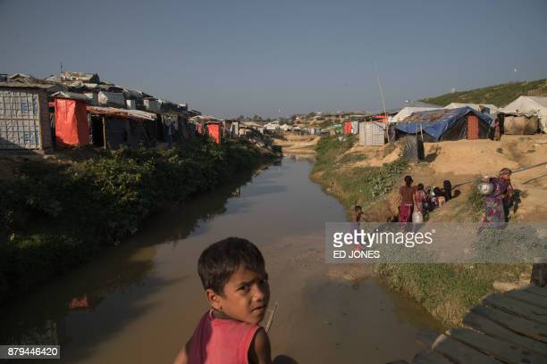 Rohingya Muslim refugees collect water from a stream at the Kutupalong refugee camp in Cox's Bazar on November 26 2017 Rohingya refugees who return...