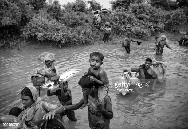 COX'S BAZAR BANGLADESH NOVEMBER 01 Rohingya Muslim refugees cross a canal as they flee over the border from Myanmar into Bangladesh at the Naf River...