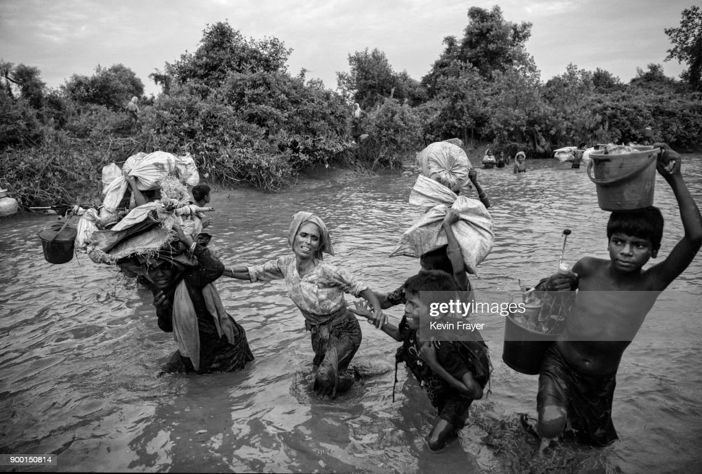 "COX'S BAZAR, BANGLADESH - NOVEMBER 01: Rohingya Muslim refugees cross a canal as they flee over the border from Myanmar into Bangladesh at the Naf River on November 1, 2017 near Anjuman Para in Cox's Bazar, Bangladesh. More than 600,000 Rohingya refugees have flooded into Bangladesh to flee an offensive by Myanmar's military that the United Nations has called ""a textbook example of ethnic cleansing"". The refugee population continues to swell further, with thousands more Rohingya Muslims making the perilous journey on foot toward the border, or paying smugglers to take them across by water in wooden boats. Hundreds are known to have died trying to escape, and survivors arrive with horrifying accounts of villages burned, women raped, and scores killed in the ""clearance operations"" by Myanmar's army and Buddhist mobs that were sparked by militant attacks on security posts in Rakhine state on August 25, 2017. What the Rohingya refugees flee to is a different kind of suffering in sprawling makeshift camps rife with fears of malnutrition, cholera, and other diseases. Aid organizations are struggling to keep pace with the scale of need and the staggering number of them — an estimated 60 percent — who are children arriving alone. Bangladesh, whose acceptance of the refugees has been praised by humanitarian officials for saving lives, has urged the creation of an internationally-recognized ""safe zone"" where refugees can return, though Rohingya Muslims have long been persecuted in predominantly Buddhist Myanmar. World leaders are still debating how to confront the country and its de facto leader, Aung San Suu Kyi, a Nobel Peace Prize laureate who championed democracy, but now appears unable or unwilling to stop the army's brutal crackdown."