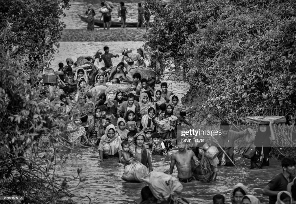 COX'S BAZAR, BANGLADESH - NOVEMBER 01: Rohingya Muslim refugees crowd a canal as they flee over the border from Myanmar into Bangladesh at the Naf River on November 1, 2017 near Anjuman Para in Cox's Bazar, Bangladesh. More than 600,000 Rohingya refugees have flooded into Bangladesh to flee an offensive by Myanmar's military that the United Nations has called 'a textbook example of ethnic cleansing'. The refugee population continues to swell further, with thousands more Rohingya Muslims making the perilous journey on foot toward the border, or paying smugglers to take them across by water in wooden boats. Hundreds are known to have died trying to escape, and survivors arrive with horrifying accounts of villages burned, women raped, and scores killed in the 'clearance operations' by Myanmar's army and Buddhist mobs that were sparked by militant attacks on security posts in Rakhine state on August 25, 2017. What the Rohingya refugees flee to is a different kind of suffering in sprawling makeshift camps rife with fears of malnutrition, cholera, and other diseases. Aid organizations are struggling to keep pace with the scale of need and the staggering number of them - an estimated 60 percent - who are children arriving alone. Bangladesh, whose acceptance of the refugees has been praised by humanitarian officials for saving lives, has urged the creation of an internationally-recognized 'safe zone' where refugees can return, though Rohingya Muslims have long been persecuted in predominantly Buddhist Myanmar. World leaders are still debating how to confront the country and its de facto leader, Aung San Suu Kyi, a Nobel Peace Prize laureate who championed democracy, but now appears unable or unwilling to stop the army's brutal crackdown.