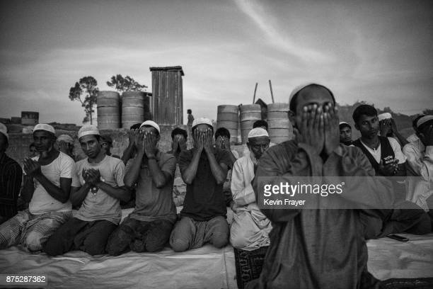 Rohingya Muslim refugees kneel as they pray at the site of a new mosque being built on October 22, 2017 at the Balukhali refugee camp in Cox's Bazar,...