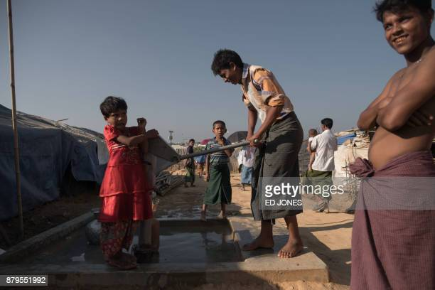 Rohingya Muslim refugees pump water at the Kutupalong refugee camp in Cox's Bazar on November 26 2017 Rohingya refugees who return to Myanmar from...