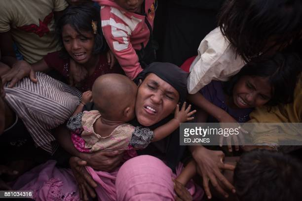 TOPSHOT Rohingya Muslim refugees react as police and officials attempt to control a surging crowd as they wait to be called to recieve food aid of...