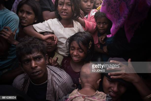 Rohingya Muslim refugees react as police and officials attempt to control a surging crowd as they wait to be called to recieve food aid of rice water...