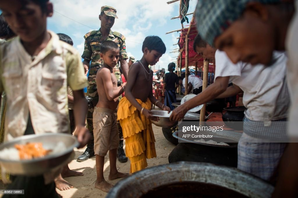 Rohingya Muslim refugees receive their daily meal at a food distribution in Balukhali refugee camp near Gumdhum on October 1, 2017. Bangladesh is to move to a camp at least 15,000 Rohingya refugees who have settled in a restive hill district near the border with Myanmar, a local official said Sunday. Most of the estimated half a million Rohingya who have arrived in southeastern Bangladesh over the last five weeks after fleeing violence in Myanmar are crammed into the camps that have sprung up on government land. /