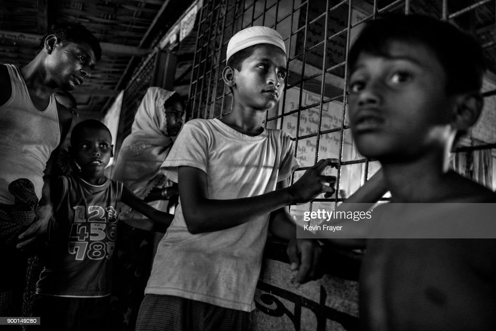 "COX'S BAZAR, BANGLADESH - OCTOBER 27:Rohingya Muslim refugees rest inside a local school being used as a temporary shelter for new arrivals on October 27, 2017 at the Kutupalong refugee camp in Cox's Bazar, Bangladesh. More than 600,000 Rohingya refugees have flooded into Bangladesh to flee an offensive by Myanmar's military that the United Nations has called ""a textbook example of ethnic cleansing"". The refugee population continues to swell further, with thousands more Rohingya Muslims making the perilous journey on foot toward the border, or paying smugglers to take them across by water in wooden boats. Hundreds are known to have died trying to escape, and survivors arrive with horrifying accounts of villages burned, women raped, and scores killed in the ""clearance operations"" by Myanmar's army and Buddhist mobs that were sparked by militant attacks on security posts in Rakhine state on August 25, 2017. What the Rohingya refugees flee to is a different kind of suffering in sprawling makeshift camps rife with fears of malnutrition, cholera, and other diseases. Aid organizations are struggling to keep pace with the scale of need and the staggering number of them — an estimated 60 percent — who are children arriving alone. Bangladesh, whose acceptance of the refugees has been praised by humanitarian officials for saving lives, has urged the creation of an internationally-recognized ""safe zone"" where refugees can return, though Rohingya Muslims have long been persecuted in predominantly Buddhist Myanmar. World leaders are still debating how to confront the country and its de facto leader, Aung San Suu Kyi, a Nobel Peace Prize laureate who championed democracy, but now appears unable or unwilling to stop the army's brutal crackdown."