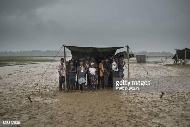 TOPSHOT Rohingya Muslim refugees take shelter from the rain during a food distribution at Nayapara refugee camp in Bangladesh's Ukhia district on...