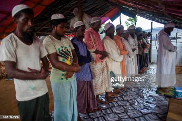 Rohingya Muslim refugees taking Asar prayer at a temporary makeshift shelter after crossing over from Myanmar into the Bangladesh side of the border,...