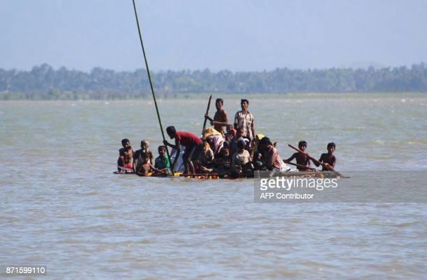 Rohingya Muslim refugees use a makeshift raft to travel from Myanmar to Bangladesh at Sha Porir Dwip in the Bangladeshi district of Teknaf on...