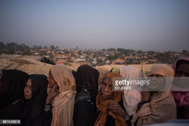 TOPSHOT Rohingya Muslim refugees wait to be called to recieve food aid of rice water and cooking oil in a relief centre at the Kutupalong refugee...