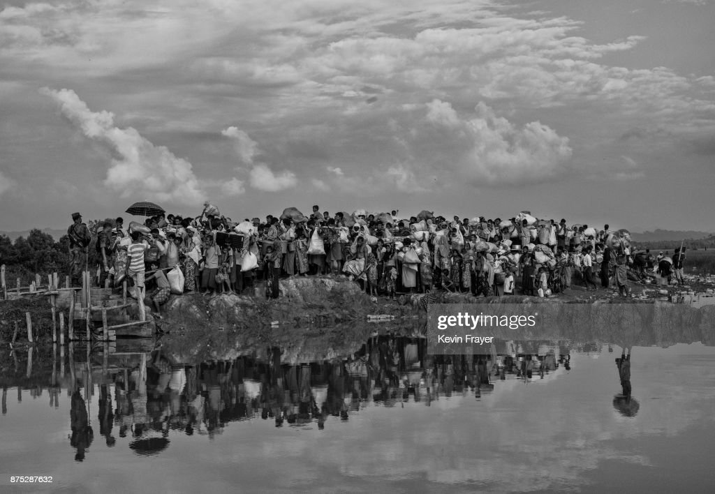 COX'S BAZAR, BANGLADESH - NOVEMBER 02: Rohingya Muslim refugees waiting to proceed to camps after crossing the border from Myanmar into Bangladesh crowd on an earthen berm close to the Naf River on November 2, 2017 near Anjuman Para in Cox's Bazar, Bangladesh. More than 600,000 Rohingya refugees have flooded into Bangladesh to flee an offensive by Myanmar's military that the United Nations has called 'a textbook example of ethnic cleansing'. The refugee population continues to swell further, with thousands more Rohingya Muslims making the perilous journey on foot toward the border, or paying smugglers to take them across by water in wooden boats. Hundreds are known to have died trying to escape, and survivors arrive with horrifying accounts of villages burned, women raped, and scores killed in the 'clearance operations' by Myanmar's army and Buddhist mobs that were sparked by militant attacks on security posts in Rakhine state on August 25, 2017. What the Rohingya refugees flee to is a different kind of suffering in sprawling makeshift camps rife with fears of malnutrition, cholera, and other diseases. Aid organizations are struggling to keep pace with the scale of need and the staggering number of them - an estimated 60 percent - who are children arriving alone. Bangladesh, whose acceptance of the refugees has been praised by humanitarian officials for saving lives, has urged the creation of an internationally-recognized 'safe zone' where refugees can return, though Rohingya Muslims have long been persecuted in predominantly Buddhist Myanmar. World leaders are still debating how to confront the country and its de facto leader, Aung San Suu Kyi, a Nobel Peace Prize laureate who championed democracy, but now appears unable or unwilling to stop the army's brutal crackdown.
