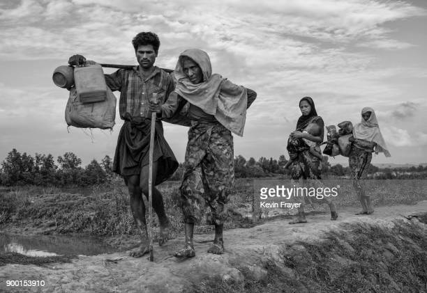 COX'S BAZAR BANGLADESH NOVEMBER 02 Rohingya Muslim refugees walk after crossing the border from Myanmar into Bangladesh close to the Naf River on...