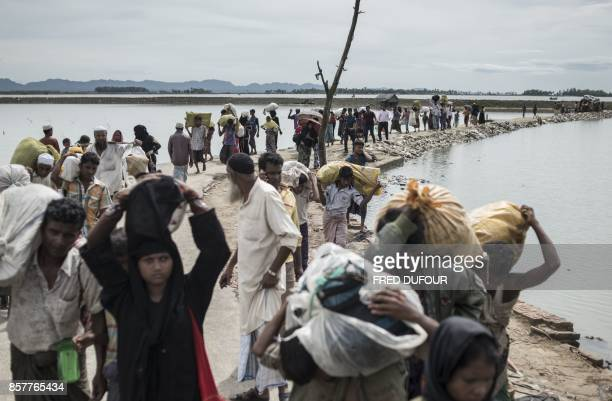 Rohingya Muslim refugees walk toward refugee camps after crossing the border from Myanmar at the Bangladeshi shores of the Naf river in Teknaf on...