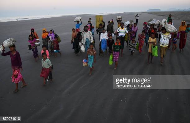 Rohingya Muslim refugees who entered Bangladesh by boat walk towards refugee camps after landing at the Saplapur beach in the Teknaf district of...