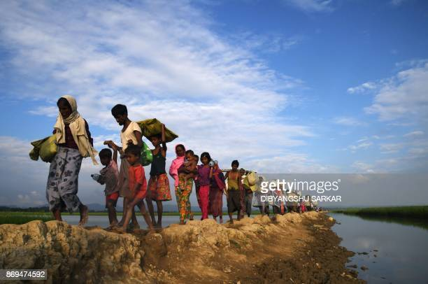 TOPSHOT Rohingya Muslim refugees who were stranded after leaving Myanmar walk towards the Balukhali refugee camp after crossing the border in...