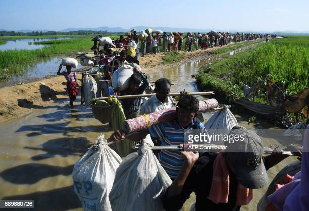 Rohingya Muslim refugees who were stranded after leaving Myanmar walk towards the Balukhali refugee camp after crossing the border in Bangladesh's...