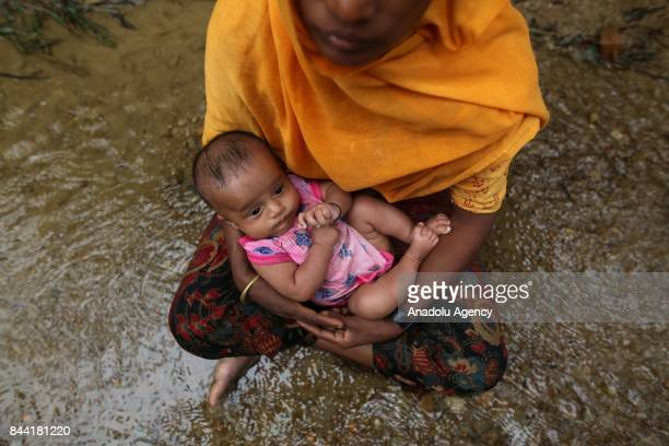 COX'S BAZAR BANGLADESH SEPTEMBER 08 A Rohingya Muslim woman fled from ongoing military operations in Myanmars Rakhine state sits in a small stream...