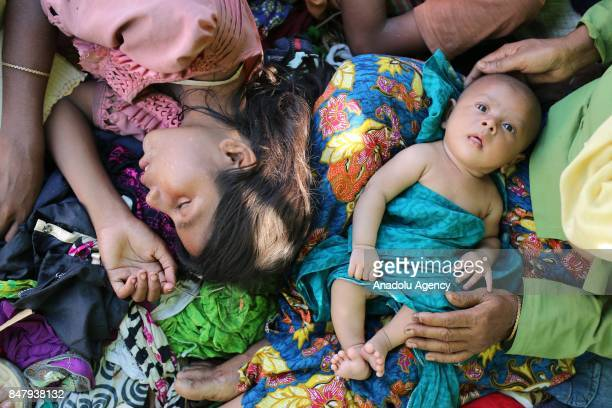 COX'S BAZAR BANGLADESH SEPTEMBER 16 A Rohingya Muslim woman fled from ongoing military operations in Myanmars Rakhine state lies down by a baby in a...