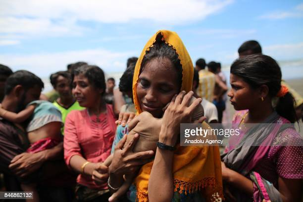 Rohingya Muslim woman holds an infant child who died when the boat they were traveling in capsized just before reaching the shore of the Bay of...