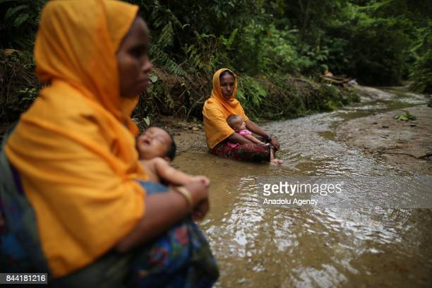 COX'S BAZAR BANGLADESH SEPTEMBER 08 Rohingya Muslim women fled from ongoing military operations in Myanmars Rakhine state sit in a small stream while...