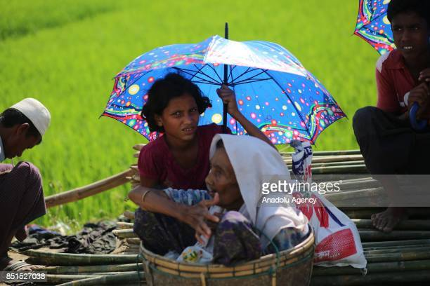 Rohingya Muslim women, fled from ongoing military operations in Myanmars Rakhine state, sit inside of a bucket at a makeshift camp in Teknaff,...
