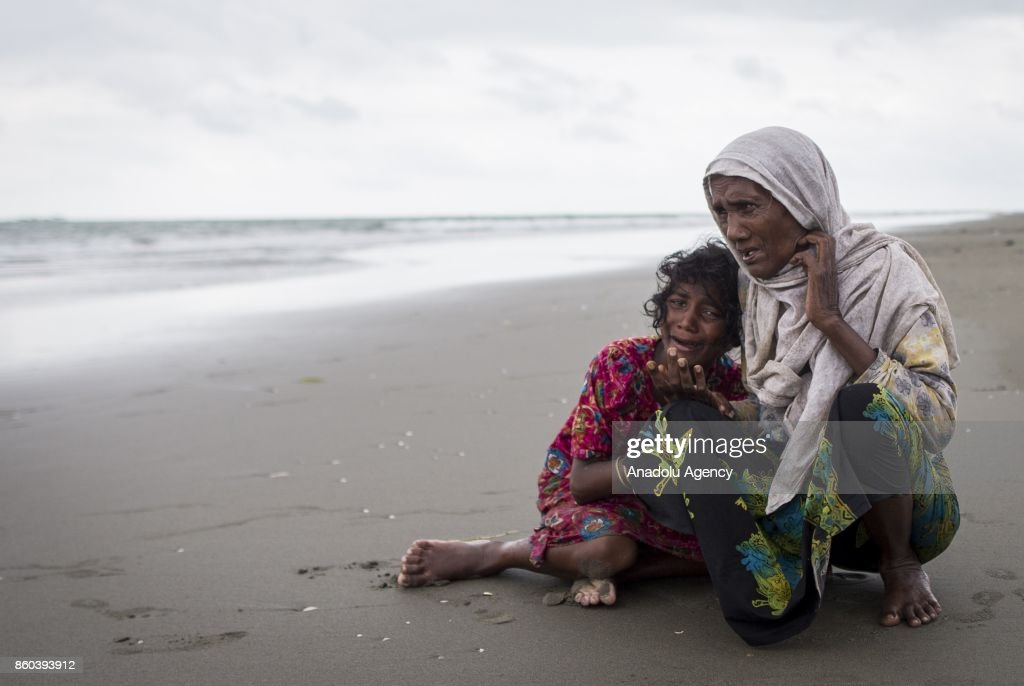 COX'S BAZAR, BANGLADESH - SEPTEMBER 29 : Rohingya Muslims are seen on the shore after crossing the Bangladesh-Myanmar border through sea borders in Shah Porir Dwip near Cox's Bazar, Bangladesh on September 29, 2017. Hundreds of Rohingyas cross land and sea borders daily to reach Bangladesh, paying 36 USD each to hire a boat to cross the borders. As the number of boats ferrying Rohingyas from Myanmar increase in the day and night hours, Bangladeshi forces try to bring the boats into order on the shore.