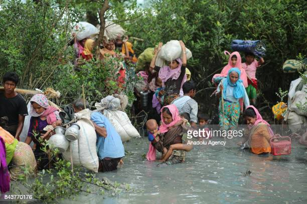 Rohingya Muslims fled from ongoing military operations in Myanmars Rakhine state walk through water after crossing Myanmar border and Naff river to...