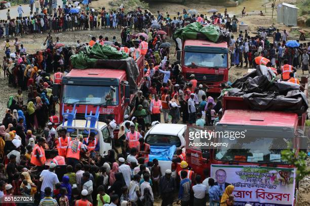 Rohingya Muslims, fled from ongoing military operations in Myanmars Rakhine state, stand in line to receive humanitarian aids at a makeshift camp in...
