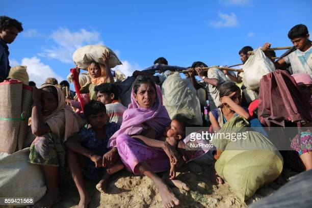 Rohingya Muslims fled from ongoing military operations in Myanmars Rakhine state make their way through muddy water after crossing the...