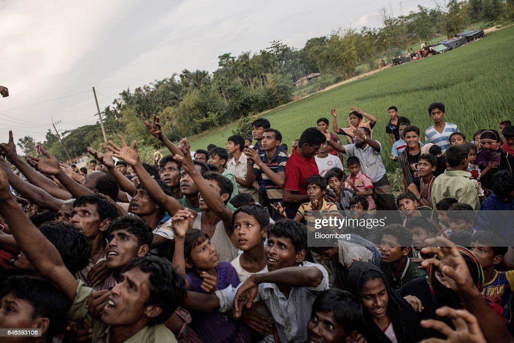 Rohingya people reach out to collect food and water rations at a newly set-up refugee camp at Balukhali in Cox's Bazar, Bangladesh, on Tuesday, Sept. 12, 2017. Myanmar's leaderAung San Suu Kyiis under attack over her response to a fresh round of violence that has seen more than 145,000minorityRohingyaMuslims flee into neighboring Bangladesh since last month. Photographer: Ismail Ferdous/Bloomberg via Getty Images