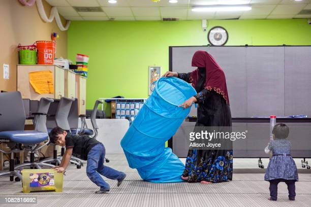 Rohingya refugee 23 year old Sakinah cleans up after English classes while her children 4 year old Shafi Rukh Khan and 1 year old Nur Sharifah play...