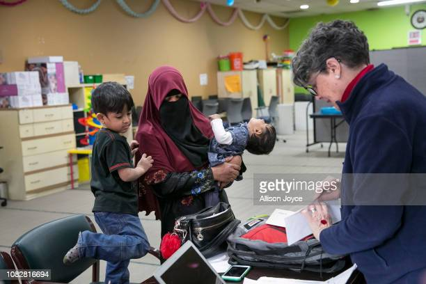 Rohingya refugee 23 year old Sakinah stands with her children 4 year old Shafi Rukh Khan and 1 year old Nur Sharifah as Assistant Director Laura...