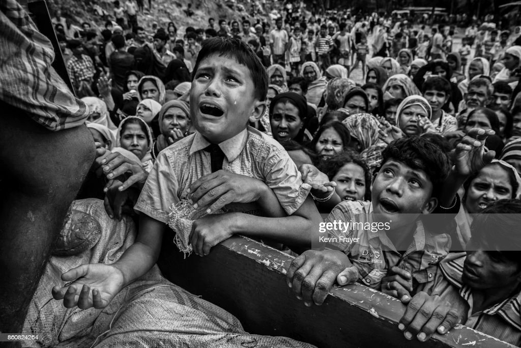 COX'S BAZAR BANGLADESH SEPTEMBER 20 A Rohingya refugee boy desperate for aid cries as he climbs on a truck distributing aid for a local NGO near the...
