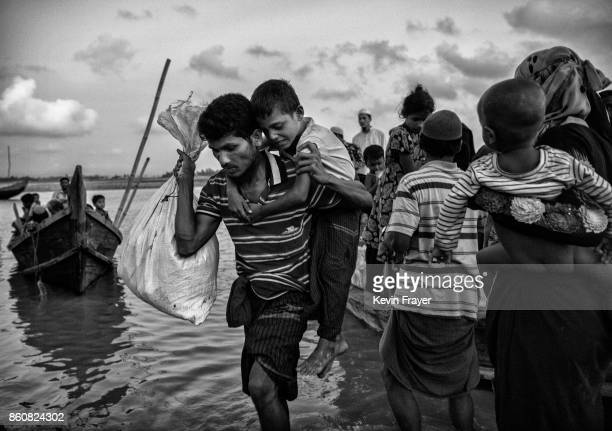COX'S BAZAR BANGLADESH SEPTEMBER 21 A Rohingya refugee boy is carried from a boat as he arriver with his family after crossing the Naf River at Shah...