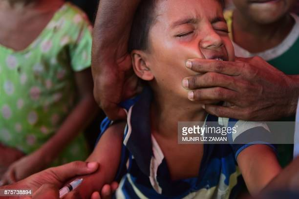 A Rohingya refugee boy reacts as an health worker administers an MMR vaccine at Hakimpara refugee camp in the Bangladeshi district of Ukhia on...