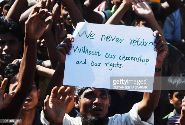 Rohingya refugee carries a placard that says We never return at a protest against a disputed repatriation programme at the Unchiprang refugee camp...
