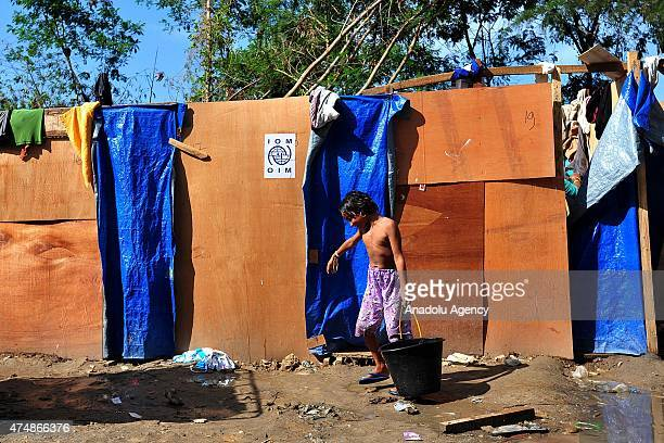 Rohingya refugee child carries a bucket of water at a temporary shelter as they cook food at Kuala Langsa, Aceh province, in Indonesia, on May 27,...