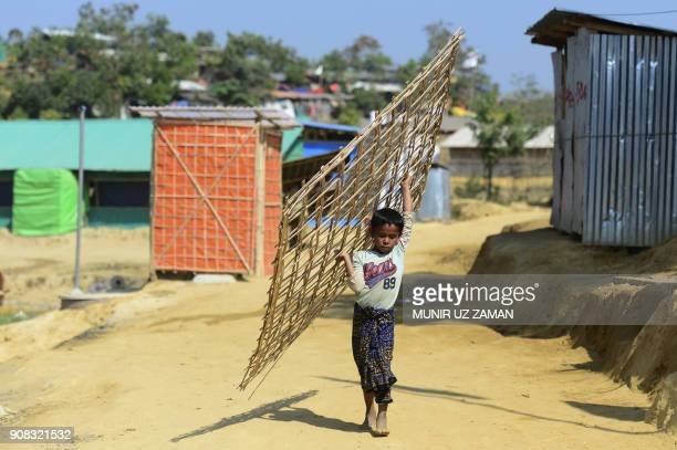 A Rohingya refugee child carries bamboo material to build an house at Burma para refugee camp in Bangladesh's Ukhia district on January 21 2018 About...