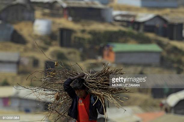 Rohingya refugee child carries wood at Balukhali refugee camp in Bangladesh's Ukhia district on January 26 2018 The repatriation of hundreds of...