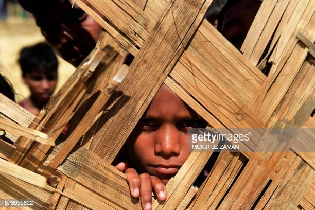 Rohingya refugee child looks into a food distribution centre at Thankhali refugee camp in Bangladesh's Ukhia district on November 14 2017 More than...